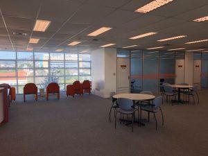 Fotografia mostrando um amplo espaço com 5 poltronas ao fundo, duas mesas redondas com cadeiras à direita e salas de estudo