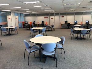 Fotografia mostrando um amplo espaço com 6 mesas redondas com cadeiras, mesas com computadores ao fundo e salas de estudos no lado esquerdo
