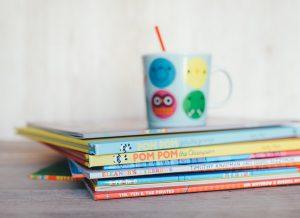 Foto de 10 livros infantis coloridos empilhados e, em cima deles, uma caneca colorida com canudo